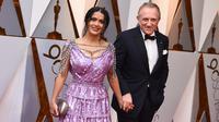 Salma Hayek dan suami, Francois-Henri Pinault  menghadiri karpet merah Piala Oscar 2018 di Los Angeles, Minggu (4/3). Tambahan aksesori seperti clutch silver dan anting chandeliernya pun membuat tampilan Salma cukup stunning. (Jordan Strauss/Invision/AP)