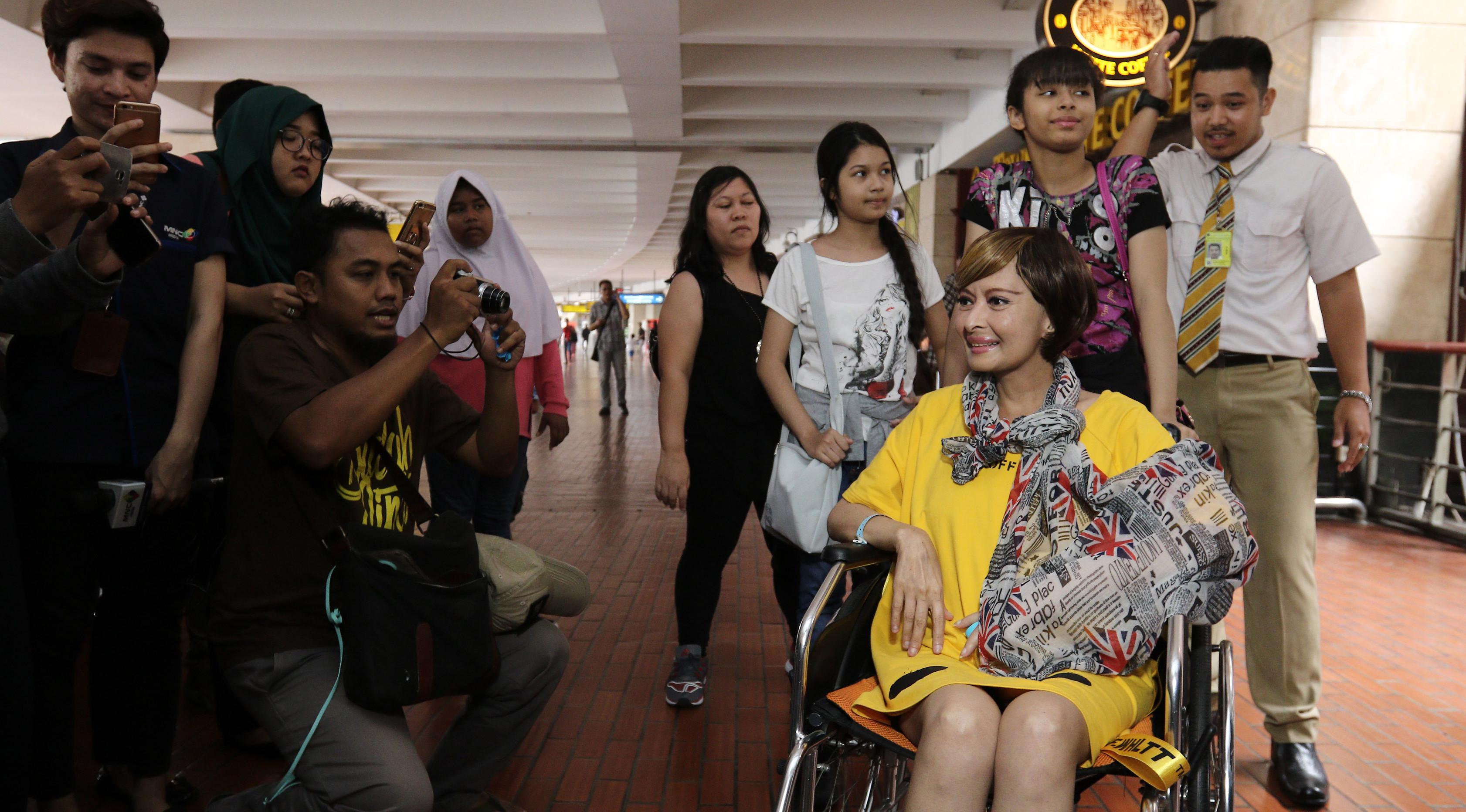 Sejumlah orang memotret Yana Zein saat tiba di bandara Bandara Soekarno Hatta, Tangerang, Minggu (28/5). Yana Zein kembali ke Tanah Air, setelah menjalani pengobatan kanker di Tiongkok. (Liputan6.com/Herman Zakharia)