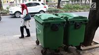 Warga melintas di depan tong sampah asal Jerman di kawasan Kalibata, Jakarta, Selasa (5/6). Gubernur Anies Baswedan mengatakan pengadaan tong sampah ini  bertujuan untuk menunjang truk sampah DKI yang sudah lebih modern. (Liputan6.com/Immanuel Antonius)