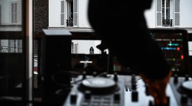 DJ Knighthood memainkan musik dari jendela apartemennya selama lockdown di Paris, Prancis (3/4/2020). DJ Knighthood beraksi menghibur tetangga yang berdiam diri di rumah sebagai upaya mencegah penyebaran virus corona Covid-19. (AFP/Philippe Lopez)