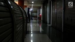 Seorang pedagang duduk di depan tokonya di pertokoan elektronik Glodok, Jakarta, Minggu (17/6). Hampir 90 persen pertokoan di Glodok tutup pada Lebaran tahun ini. (Liputan6.com/JohanTallo)