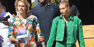 Hailey Baldwin dan Justin Bieber terlihat santai. Justin memakai kemeja hawa dengan jean pendek. Semenara Hailey menggunakan rok denim hijau yang matching dengan atasannya. (SPLASHNEWS COM/HollywoodLife)