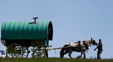Anggota komunitas saat menarik kudanya yang dipasang karavan untuk mengikuti kegiatan tradisional selama Horse Fair di Westmorland , Inggris utara , 2 Juni 2016. Sejumlah penunggang atau penyuka kuda mengikuti acara ini. (REUTERS / Phil Noble)