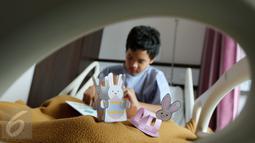 Seorang pasien anak sedang membuat prakarya dalam rangka merayakan Paskah di Rumah Sakit Siloam Semanggi, Jakarta, Minggu (16/04). Kegiatan tersebut sebagai bagian dari program Customer Centric Initiatives. (Liputan6.com/Fery Pradolo)