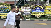 Pelayat melintasi karangan bunga duka cita untuk mendiang Eka Tjipta Widjaja di depan Rumah Duka Sentosa RSPAD Gatot Soebroto, Jakarta, Minggu (27/1). Pendiri Sinar Mas Group tersebut meninggal dunia pada 26 Januari 2019. (Merdeka.com/Iqbal Nugroho)