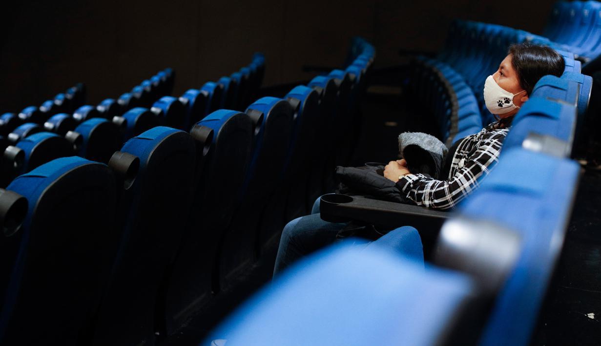 Seorang penonton menunggu dimulainya sebuah film di teater dengan hanya segelintir orang, di bioskop Cineteca Nacional di Mexico City, Rabu (12/8/2020). Setelah ditutup hampir lima bulan akibat Corona, bioskop di ibu kota Meksiko dibuka kembali dengan kapasitas 30%. (AP Photo/Rebecca Blackwell)