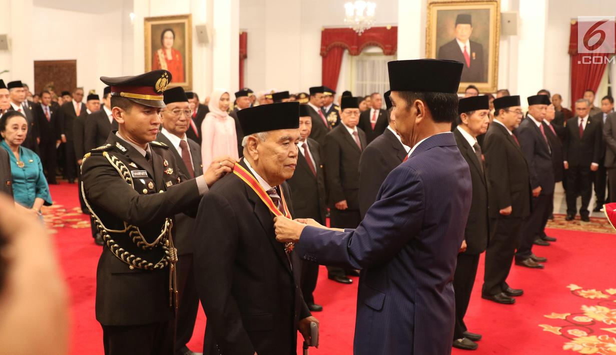 Presiden Joko Widodo atau Jokowi (kanan) menyematkan tanda kehormatan kepada tokoh nasional di Istana Negara, Jakarta, Kamis (15/8/2019). Sebanyak 29 orang mendapat gelar tanda kehormatan Bintang Mahaputra Utama dan Bintang Jasa Utama dalam rangka peringatan HUT ke-74 RI. (Liputan6.com/Angga Yuniar)