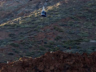 Wisatawan yang terperangkap di kereta gantung dievakuasi di Gunung El Teide, Taman Nasional El Teide, Pulau Canary, Spanyol, Rabu (15/3). Sekitar 60 wisatawan terperangkap di dua kereta gantung saat menuju puncak Gunung El Teide. (Desiree Martin/AFP)