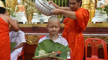 Biksu mengguyur kepala salah satu anak, yang diselamatkan dari gua di Thailand, pada upacara pentahbisan di Kuil Wat Phra That Doi Wao, Chiang Rai, Selasa (24/7). Sebanyak 11 remaja menjalani ritual menjadi biksu. (Panumas Sanguanwong/THAI NEWS PIX/AFP)