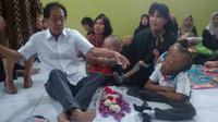 Irwan Hidayat dan Anne Avanti bercengkerama dengan Lanjar, penyandang Hydrocephalus yang sudah 13 tahun. (foto: Liputan6.com / edhie prayitno ige)
