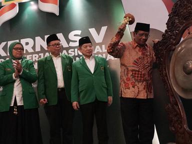 Menko Polhukam Mahfud Md didampingi Plt Ketua Umum PPP Suharso Monoarfa memukul gong untuk membuka Musyawarah Kerja Nasional (Mukernas) ke V PPP di Jakarta, Sabtu (14/12/2019). Salah satu agenda yang akan dibahas dalam acara ini adalah pelaksanaan Muktamar PPP. (Liputan6.com/Angga Yuniar)