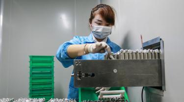 Karyawan wanita saat bekerja di sebuah pabrik baterai di Huaibei di provinsi Anhui timur China (6/3). Huaibei adalah rumah bagi banyak perusahaan kimia, konstruksi, mesin, tekstil, listrik, elektronik, dan perusahaan industri mineral. (AFP Photo/STR)