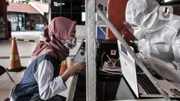 Tenaga kesehatan saat mendata hasil tes antigen di Terminal Kampung Rambutan, Jakarta, Minggu (3/1/2021). Pengelola Terminal Kampung Rambutan menyediakan tes antigen bagi penumpang yang baru tiba jika tidak memiliki surat kesehatan dengan harga Rp150 ribu per orang. (merdeka.com/Iqbal S. Nugroho)