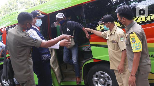 Petugas menurunkan warga yang terjaring razia penggunaan masker dari kendaraan di Kelurahan Sudimara Barat, Kota Tangerang, Kamis (27/5/2021). Mereka yang terjaring razia diminta untuk melakukan tes GeNose C19 guna mencegah penularan virus corona Covid-19. (Liputan6.com/Angga Yuniar)