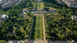 """Foto udara dari lukisan raksasa """"Beyond Walls"""" karya seniman jalanan Prancis, Saype, yang terbentang di halaman Champs de Mars, depan Menara Eiffel di Paris, 13 Juni 2019. Menggunakan cat ramah lingkungan, lukisan itu bergambar seperti tangan-tangan raksasa saling bergandengan. (Eric FEFERBERG/AFP)"""