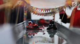 """Anak-anak mengikuti kontes kapal otok-otok (mainan tradisional berbentuk kapal dari kaleng bekas) di galeri kertas Studio Hanafi, Depok, Sabtu (16/2). Perlombaan kapal otok-otok tersebut bertema """"Oom otok-otok Oom"""". (Liputan6.com/Herman Zakharia)"""