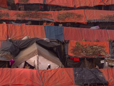 Seorang pria Muslim Rohingya berjalan melewati tenda-tenda pengungsian di kamp pengungsi Jamtoly, Bangladesh (15/1). Etnis Rohingya yang mengungsi di Bangladesh akan segara dipulangkan ke Myanmar.  (AP Photo / Manish Swarup)