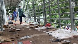 Sampah berserakan di koridor Jembatan Penyebrangan Orang (JPO) Jalan Medan Merdeka Barat, Jakarta, Selasa (1/1). Pasca malam perayaan pergantian tahun JPO Medan Merdeka Barat masih tampak kotor. (Liputan6.com/Helmi Fithriansyah)