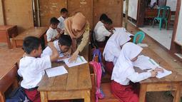 Siswa melakukan aktivitas belajar di bawah tenda darurat di SDN Mutiara, Kampung Pasir Bayur, Cibeber II, Bogor, Selasa (3/4). Mereka terpaksa belajar di luar karena bangunan sekolah yang berdiri sejak tahun 2009 itu rusak berat. (Merdeka.com/Arie Basuki)