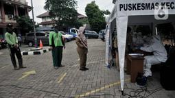 Peseta antre saat akan melakukan tes swab COVID-19 di Kantor Kecamatan Kramat Jati, Jakarta, Selasa (16/6/2020). Puskesmas Kecamatan Kramat Jati menggelar tes swab bagi seluruh pegawai instansi pemerintahan untuk memutus rantai penyebaran COVID-19. (merdeka.com/Iqbal Nugroho)