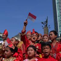 Seorang murid sekolah minggu Gereja Eban Haezer mengenakan baju adat sambil melambaikan bendera nasional di Bundaran HI Jakarta, Minggu (21/8). Menyanyikan lagu Indonesia Raya dan lagu daerah, mereka memperingati HUT RI ke 71. (Liputan6.com/Angga Yuniar)