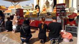 Pengunjung berdoa di kawasan kuil Golden Budha di kota Bangkok, Thailand, Sabtu (17/12). Salah satu biksu yang ada di kuil tersebut memprediksi hasil laga final kedua Piala AFF 2016 antara Thailand melawan Indonesia. (Liputan6.com/Helmi Fithriansyah)