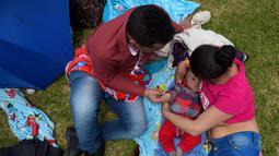 Seorang wanita menyusui anaknya didampingi suaminya selama Pekan Menyusui Dunia di taman Los Novios, Bogota, Kolombia, (3/8). Pekan Menyusui Sedunia diikuti lebih dari 170 negara. (AFP Photo/Raul Arboleda)