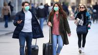 Orang-orang memakai masker berjalan di Milan, Italia (24/2/2020). Kepala Departemen Perlindungan Sipil sekaligus Komisaris Luar Biasa untuk Darurat Coronavirus, Angelo Borrelli mengatakan enam orang meninggal dan 222 lainnya teruji positif infeksi COVID-19 di Italia. (Xinhua/Daniele Mascolo)