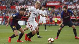 Gelandang Barcelona, Sergi Roberto, berebut bola dengan pemain Sevilla, Simon Kjaer, pada laga La Liga di Stadion Ramon Sanchez Pizjuan, Sabtu (23/2). Barcelona menang 4-2 atas Sevilla. (AP/Miguel Morenatti)