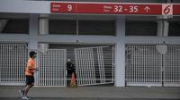 Warga berolahraga melintasi pintu masuk zona 9 Stadion Utama Gelora Bung Karno yang rusak pada Final Piala Presiden 2018, Jakarta, Minggu (18/2). Kerusakan disebabkan suporter salah satu tim sepakbola yang merangsek masuk. (Liputan6.com/Faizal Fanani)