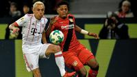 Aksi pemain Leverkusen, Leon Patrick Bailey (kanan) berebut bola dengan pemain Bayern Munchen, Rafinha pada lanjutan Budesliga di Bay Arena, Laverkusen, (12/1/2018). Bayern Munchen menang 3-1. (AFP/Sascha Schuermann)