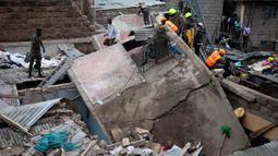 Petugas penyelamat mengevakuasi korban yang terjebak puing bangunan lima lantai yang runtuh di daerah permukiman di ibu kota Kenya, Nairobi, Minggu (4/6). Belum jelas yang menjadi sebab runtuhnya gedung tersebut. (AP Photo/Ben Curtis)