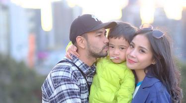 Pemilik nama lengkap Rafathar Malik Ahmad tengah diapit mesra oleh kedua orang tuanya, Raffi Ahmad dan Nagita Slavina. Mereka bertiga menikmati suasana sore hari di Melbourne, Australia. (Liputan6.com/IG/@raffinagita1717)