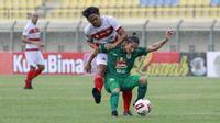 Gelandang PSS Sleman, Kim Jeffrey Kurniawan (kanan) berebut bola dengan bek Madura United, Rendika Rama dalam laga Grup C Piala Menpora 2021 di Stadion Si Jalak Harupat, Bandung, Selasa (23/3/2021). (Bola.com/M Iqbal Ichsan)