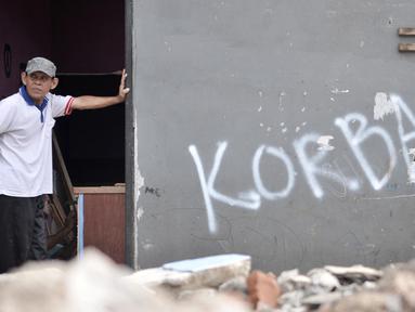 Warga berdiri diantara puing sisa bangunan rumah yang terkena gusuran proyek Tol Becakayu, Cipinang Besar Utara, Jakarta, Senin (30/12/2019). Tercatat 900 rumah warga di 3 RW, yakni RW 001, 002, dan 003 Kelurahan Cipinang Besar Utara terkena gusuran proyek Tol Becakayu.(merdeka.com/Iqbal S. Nugroho)