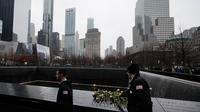 "Orang-orang menaruh bunga mawar di atas nama korban pengeboman World Trade Center 1993 pada upacara peringatan ""Tragedi 9/11"" di New York, Rabu (26/2/2020). 27 tahun lalu teroris meledakkan bom di sebuah garasi parkir World Trade Center (WTC) yang menewaskan enam korban. (AP/John Minchillo)"