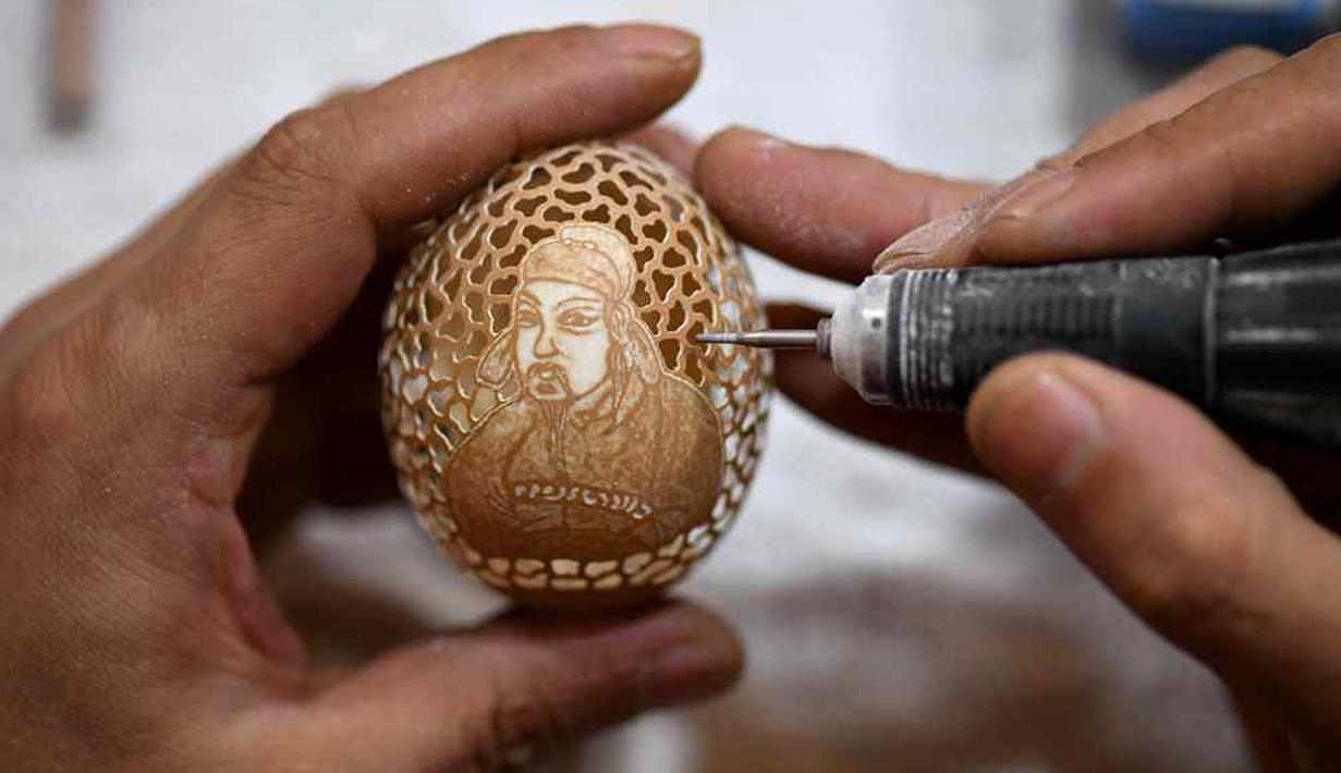 """Zhang Xiaohe membuat kerajinan ukiran telur di sebuah lokakarya warisan budaya takbenda di Shijiangzhuang, China pada 17 April 2020. Ukiran telur sering disebut """"seni yang paling rapuh"""", karena membutuhkan ketelitian dan perhatian tinggi sebelum, selama dan setelah pembuatannya. (Xinhua/Chen Qibao)"""