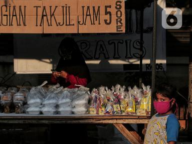 Seorang anak berdiri di depan tumpukan takjil yang akan dibagikan di Jalan Cempaka Putih Raya, Jakarta, Senin (11/5/2020). Setiap hari selama Ramadan, masyarakat sekitar membagikan 350 takjil kepada warga kurang mampu dan terdampak virus corona COVID-19. (Liputan6.com/Johan Tallo)
