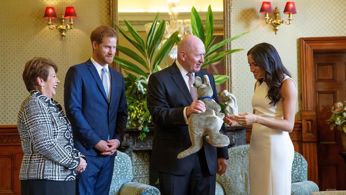 Meghan Markle menerima hadiah boneka kangguru dari Gubernur Jenderal Australia Sir Peter Cosgrove dalam kunjungan resminya bersama Pangeran Harry di Sydney, Selasa (16/10). Meghan tampak senang menerima hadiah bayi pertamanya. (Steve Christo / POOL / AFP)