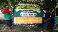 Pekerja menaruh Karangan bunga di rumah duka tokoh PBNU KH Hasyim Muzadi di Ponpes Al-Hikam, Depok, Jawa Barat, Kamis (16/3). Karangan bunga mulai berdatangan pascameninggalnya KH Hasyim Muzadi. (Liputan6.com/Immanuel Antonius)