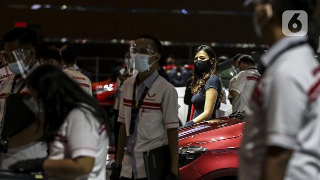 SPG berdiri dekat mobil yang dipamerkan di Indonesia International Motor Show (IIMS) Hybrid 2021, JiExpo Kemayoran, Jakarta, Kamis (16/4/2021). Acara digelar secara daring dan kunjungan langsung dengan pembatasan kapasitas dan penerapan protokol kesehatan COVID-19. (Liputan6.com/JohanTallo)