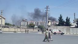 Warga berjalan ketika kepulan asap terlihat setelah ledakan besar di Kabul, Afghanistan, Senin (1/7/2019). Ledakan besar menyebabkan puluhan orang dilarikan ke rumah sakit, baik akibat terkena puing bangunan maupun asap tebal, demikian sebagaimana dikutip dari Al Jazeera pada Senin (1/7/2019). (AFP