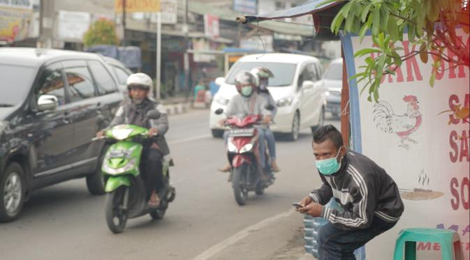 Seorang penagih utang tengah memperhatikan nomor polisi sepeda motor (Liputan6.com/Balgoraszky Marbun)