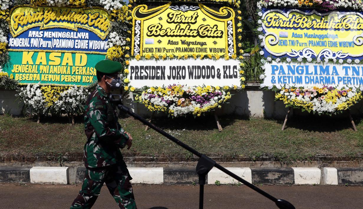 Prajurit TNI melintas di depan karangan bunga tanda duka cita atas meninggalnya mantan KSAD Jenderal TNI (Purn) Pramono Edhie Wibowo di kawasan Puri Cikeas, Kab Bogor, Jabar, Minggu (14/6/2020). Pramono Edhie Wibowo wafat di usia 65 tahun akibat serangan jantung. (Liputan6.com/Helmi Fithriansyah)