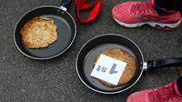Kaia Larkas usai memenangkan lomba lari sembari membawa wajan berisi pancake di Kota Olney, Buckinghamshire, Inggris, Selasa (28/2). Lomba yang digelar pada Hari Pancake atau Pancake Day ini diadakan satu hari menjelang Rabu Abu. (AP Photo/Alastair Grant)