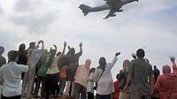 Sejumlah keluarga pengantar calon haji asal Labuhanbatu melambaikan tangan ke arah pesawat yang membawa rombongan calon haji kloter pertama, di Bandara Polonia Medan, Sumut, Senin (11/10). (Antara)
