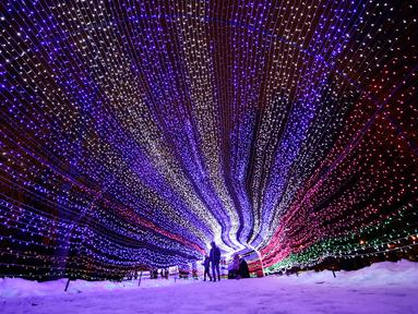 Pengunjung berjalan di dalam hiasan cahaya lampu di sebuah taman di Minsk, Belarus (28/12). Setelah matahari terbenam, orang-orang berdatangan untuk menikmati pameran cahaya lampu yang dipasang di seluruh taman. (AP Photo/Grits Sergei)