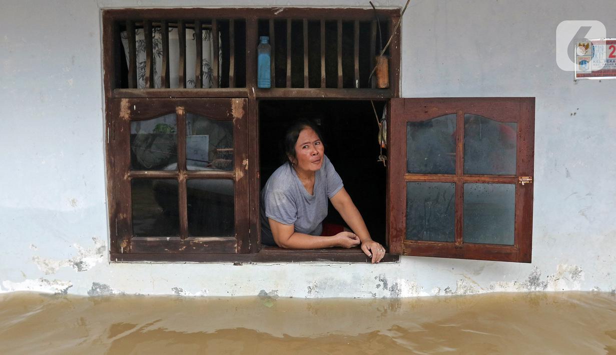 Warga melihat keluar jendela saat banjir di RW 07, Kelurahan Pekayon, Jakarta Timur, Sabtu (20/2/2021). Banjir di kawasan tersebut terjadi akibat curah hujan yang tinggi. (Liputan6.com/Herman Zakharia)