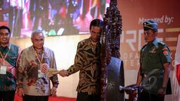 Presiden Jokowi memukul gong sebagai tanda pembukaan acara  International Trade and Investement Summit yang diselenggarakan oleh Asosiasi Pemerintahan Kabupaten Seluruh Indonesia (Apkasi) di Jakarta, Rabu (13/5/2015). (Liputan6.com/Faizal Fanani)
