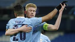 Pemain Manchester City, Kevin De Bruyne melakukan selebrasi bersama Riyad Mahrez usai mencetak gol ke gawang Borussia Dortmund pada laga Liga Champions di Stadion Etihad, Rabu (7/4/2021). City menang dengan skor 2-1. (AP/Dave Thompson)
